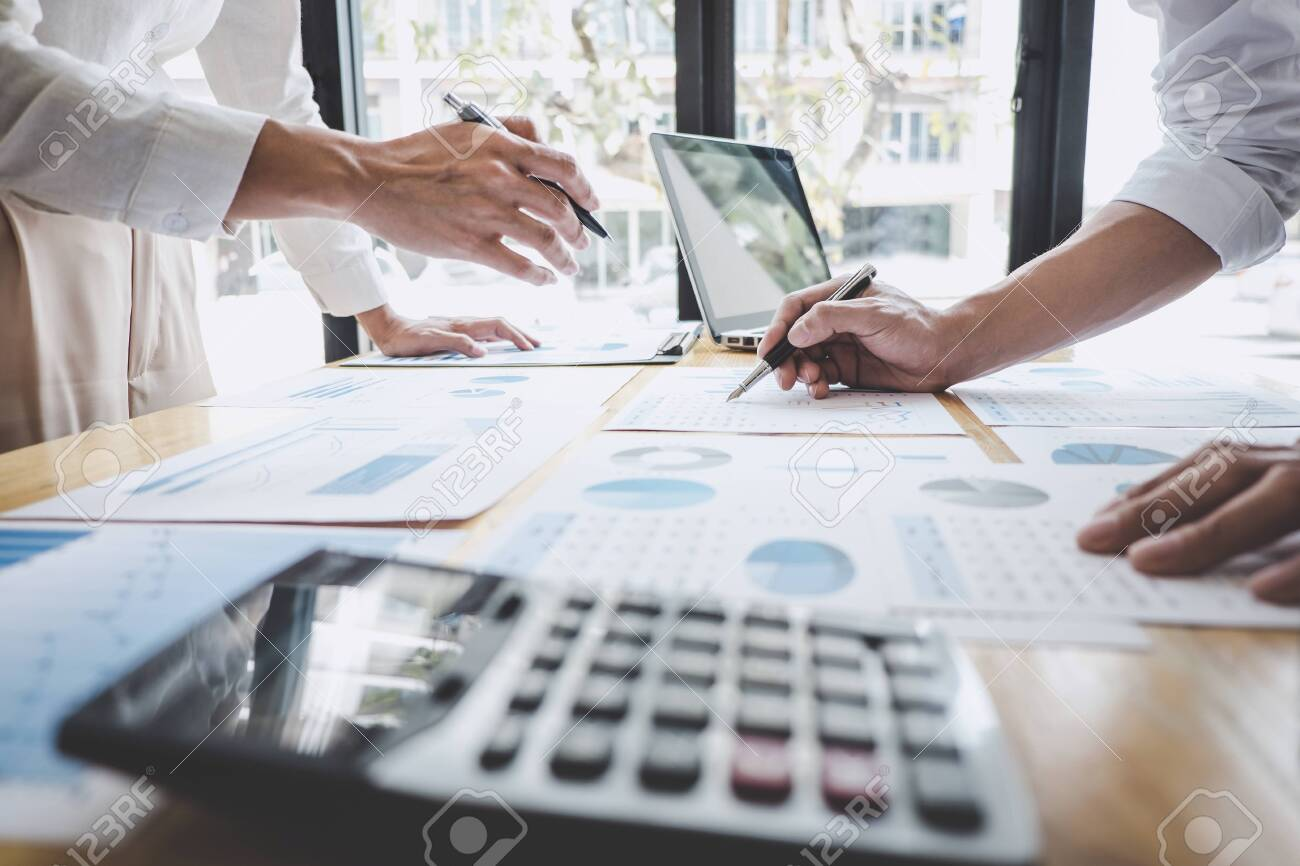 Business casual team manager having a discussion with new project success financial statistics, Partner meeting professional investor working start up project for both company with document. - 120859957