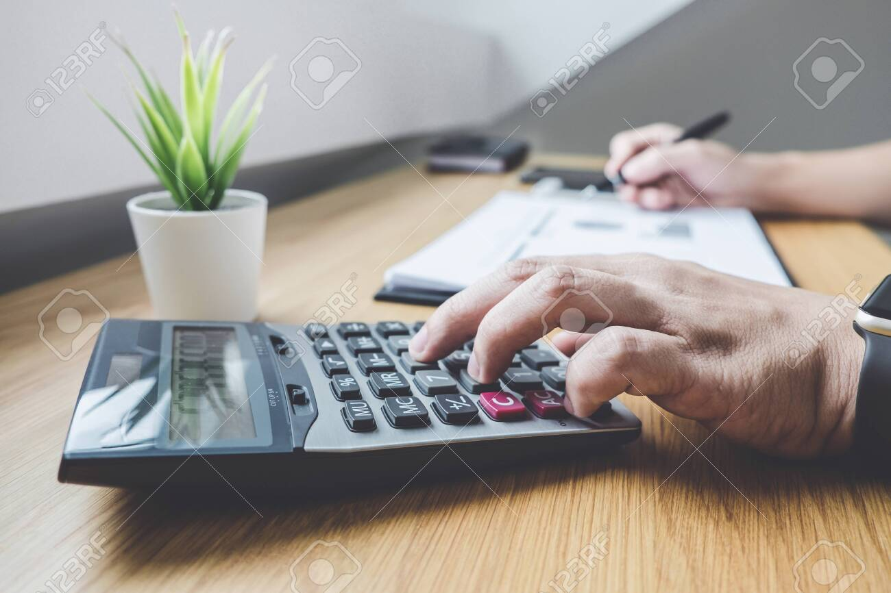 Businessman working on a graph document financial report and analysis calculation investment cost with calculator at office desk and other objects around. - 120662758