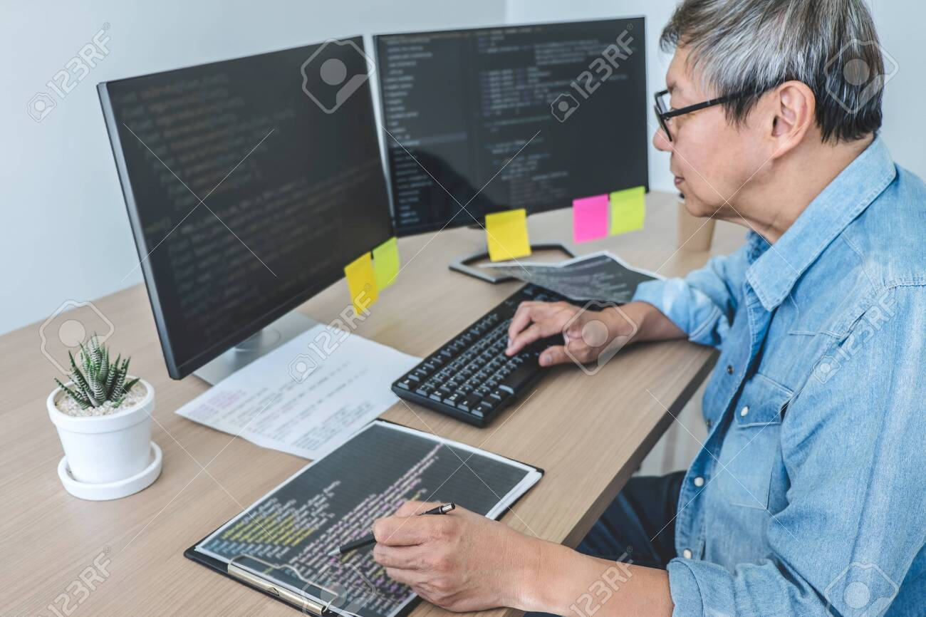 Senior Professional programmer working at developing programming and website working in a software develop company office, writing codes and typing data code. - 147823100