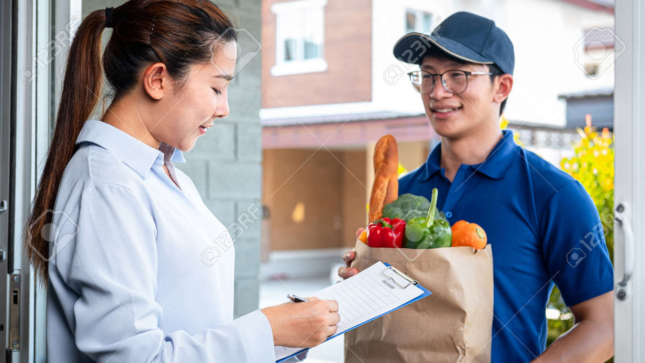Asian woman customer order food delivery online and standing in front of the house to receive grocery of food, fruit, vegetable and sign on food delivery bill from courier - 169421162