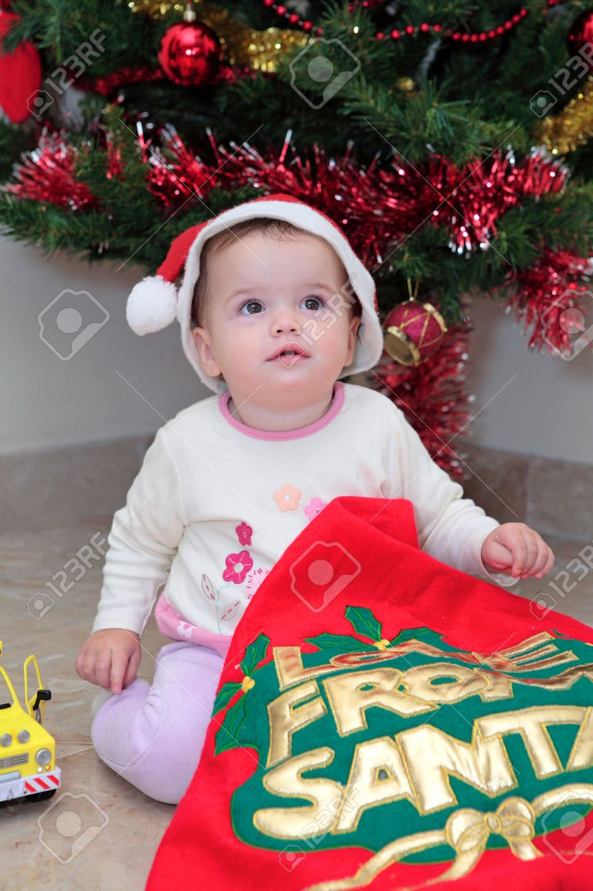 Baby Girl Opening Christmas Presents By The Xmas Tree Stock Photo ...