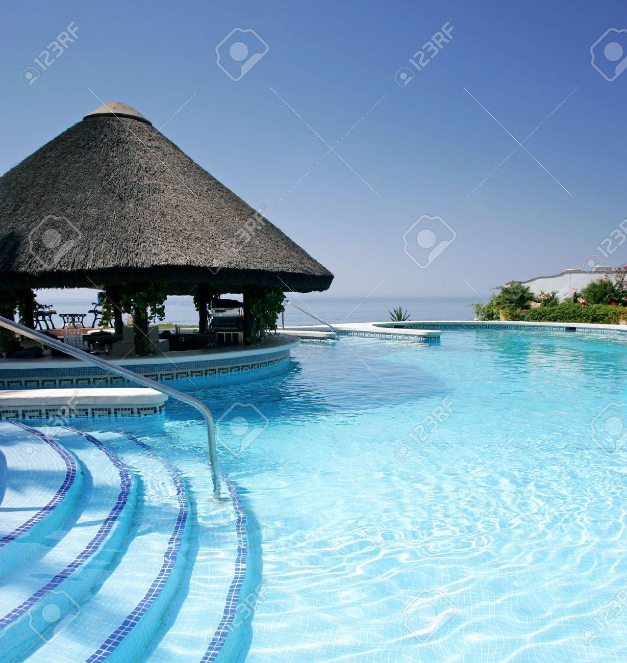 tiki hut and bar by steps of swimming pool of luxury hotel on a bright sunny