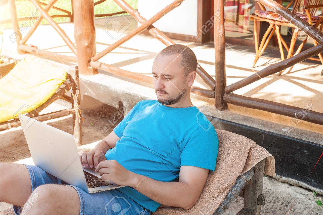Outstanding A Man Sitting On A Wicker Lounge Chair And Working At The Computer Andrewgaddart Wooden Chair Designs For Living Room Andrewgaddartcom
