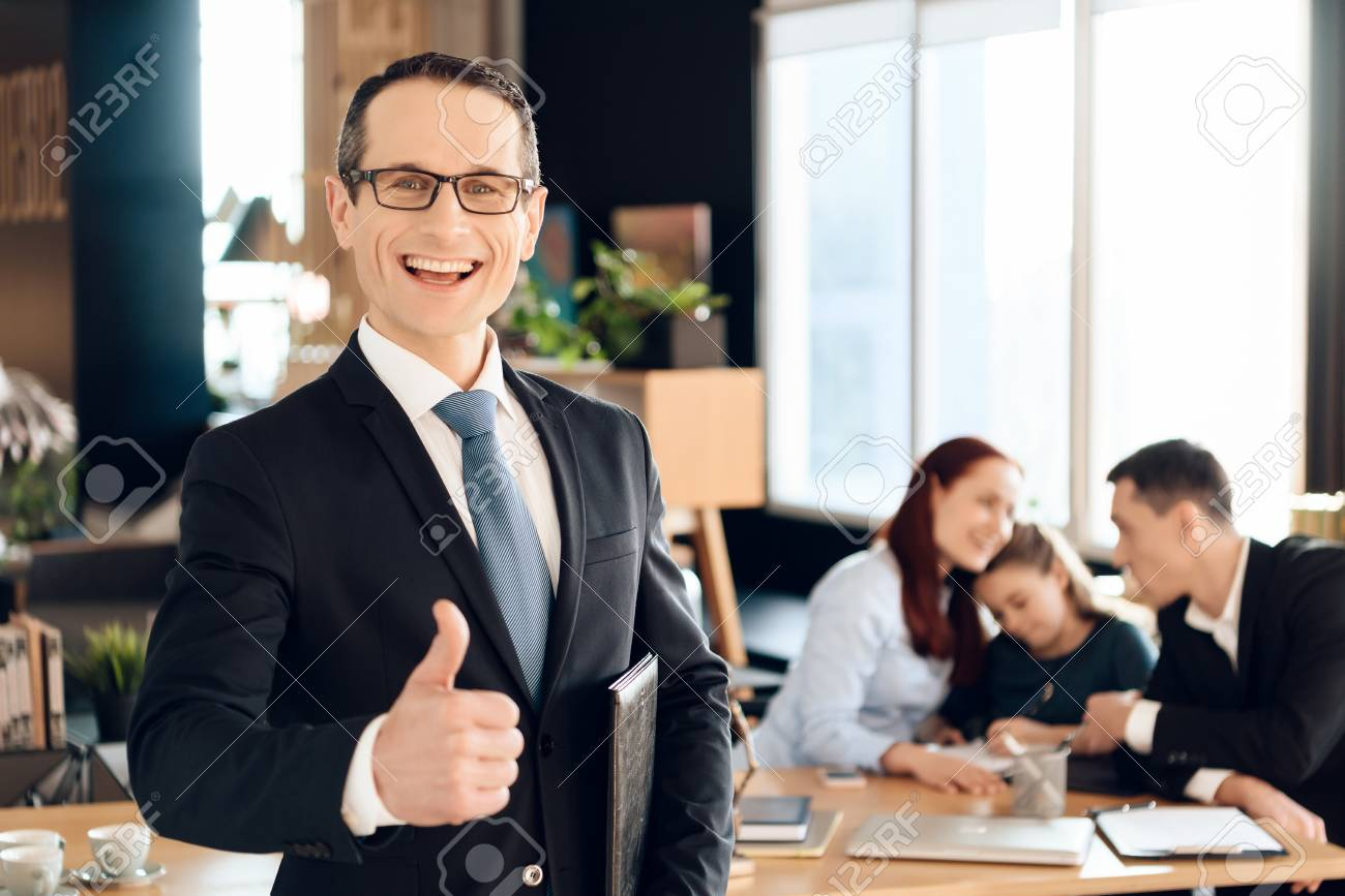 Confident adult man in suit stands in front of office of family