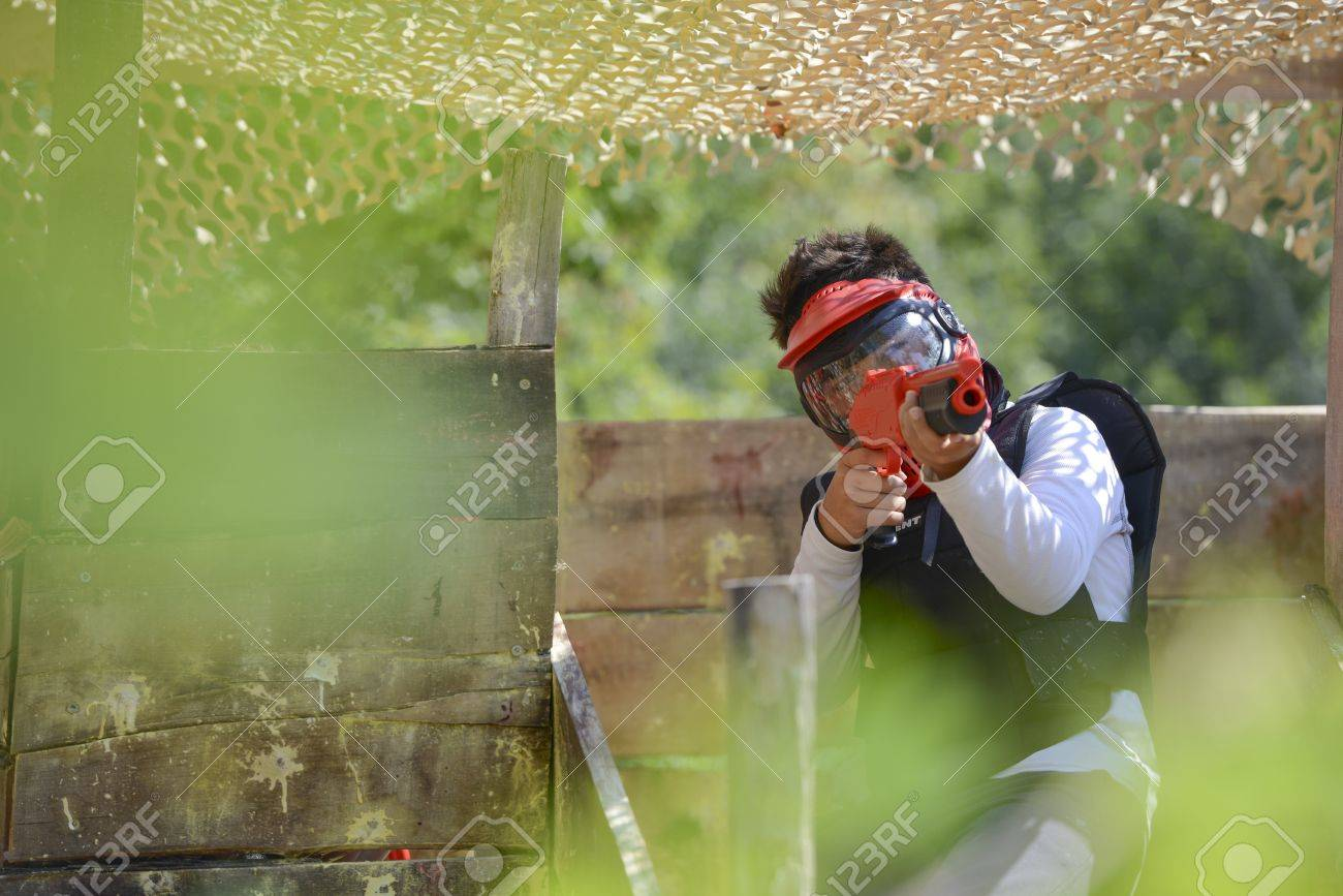 Young children playing paintball in the woods Stock Photo - 21933596