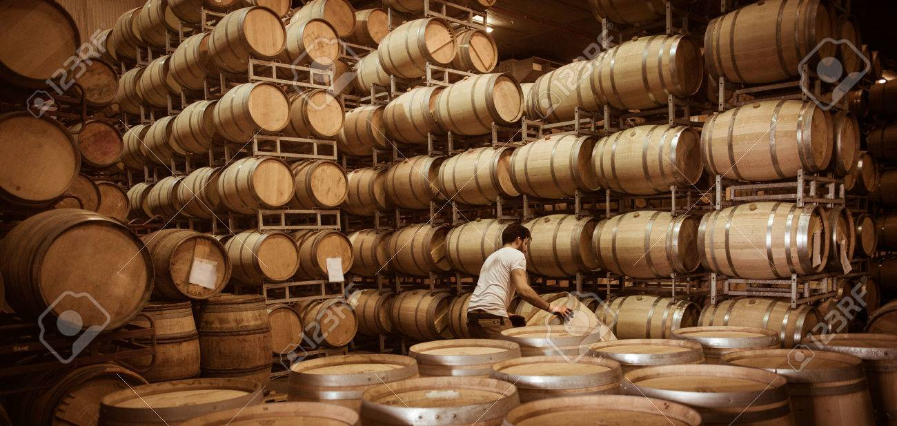 Winemaker barrels moving up or down by rolling on the ground in a large storage cellar, Bordeaux Vineyard, France Stock Photo - 59466704