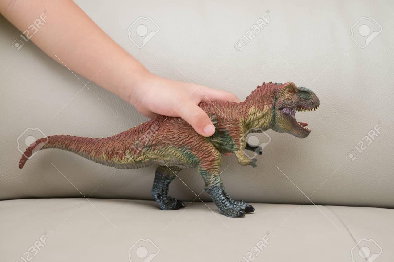 自宅のソファーにティラノサウルスのおもちゃをキャッチ子供手 の写真