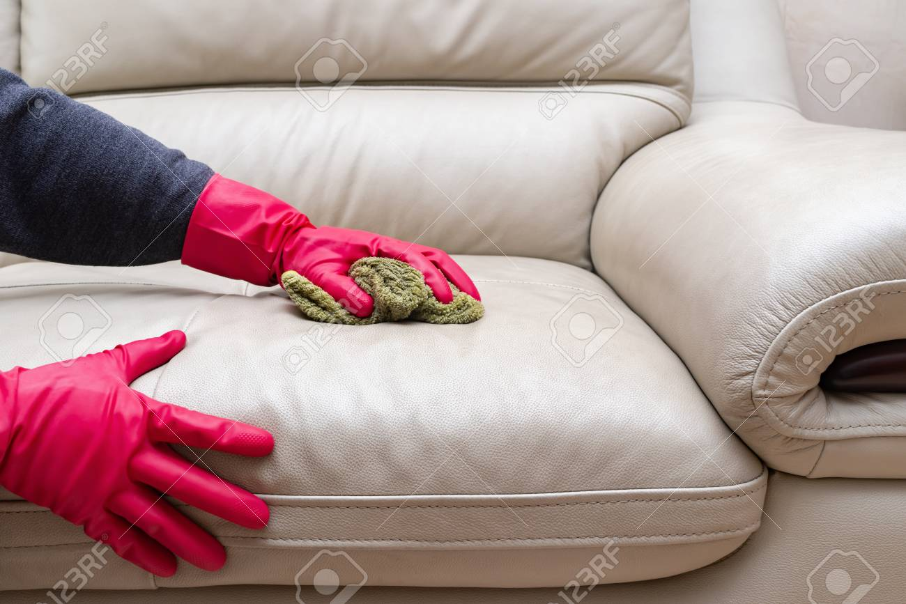 - Side View Of Man Cleaning Leather Sofa At Home With Wet Towel