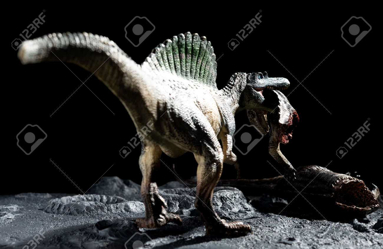 spinosaurus bitting a tenontosaurus body on a ground with craters - 159712464