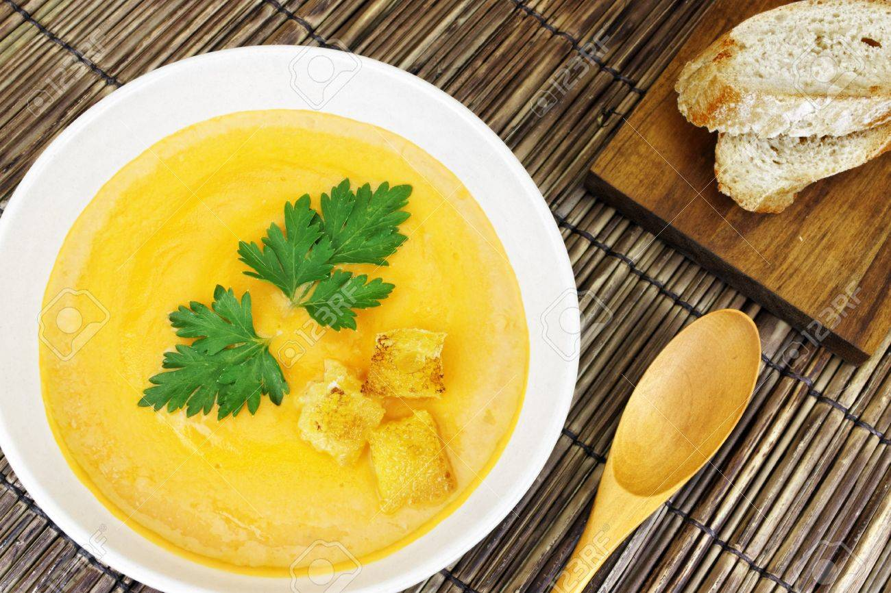A delicious carrot soup served with bread on a bamboo mat. Stock Photo - 12431706