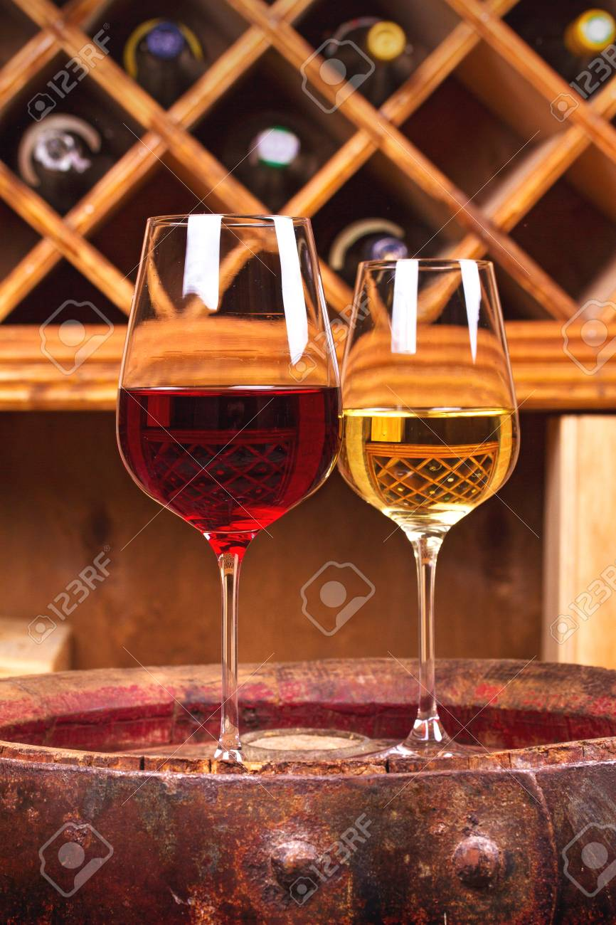 Glasses and bottles of red and white wine on old barrel in wine cellar. Wineglasses & Glasses And Bottles Of Red And White Wine On Old Barrel In Wine ...