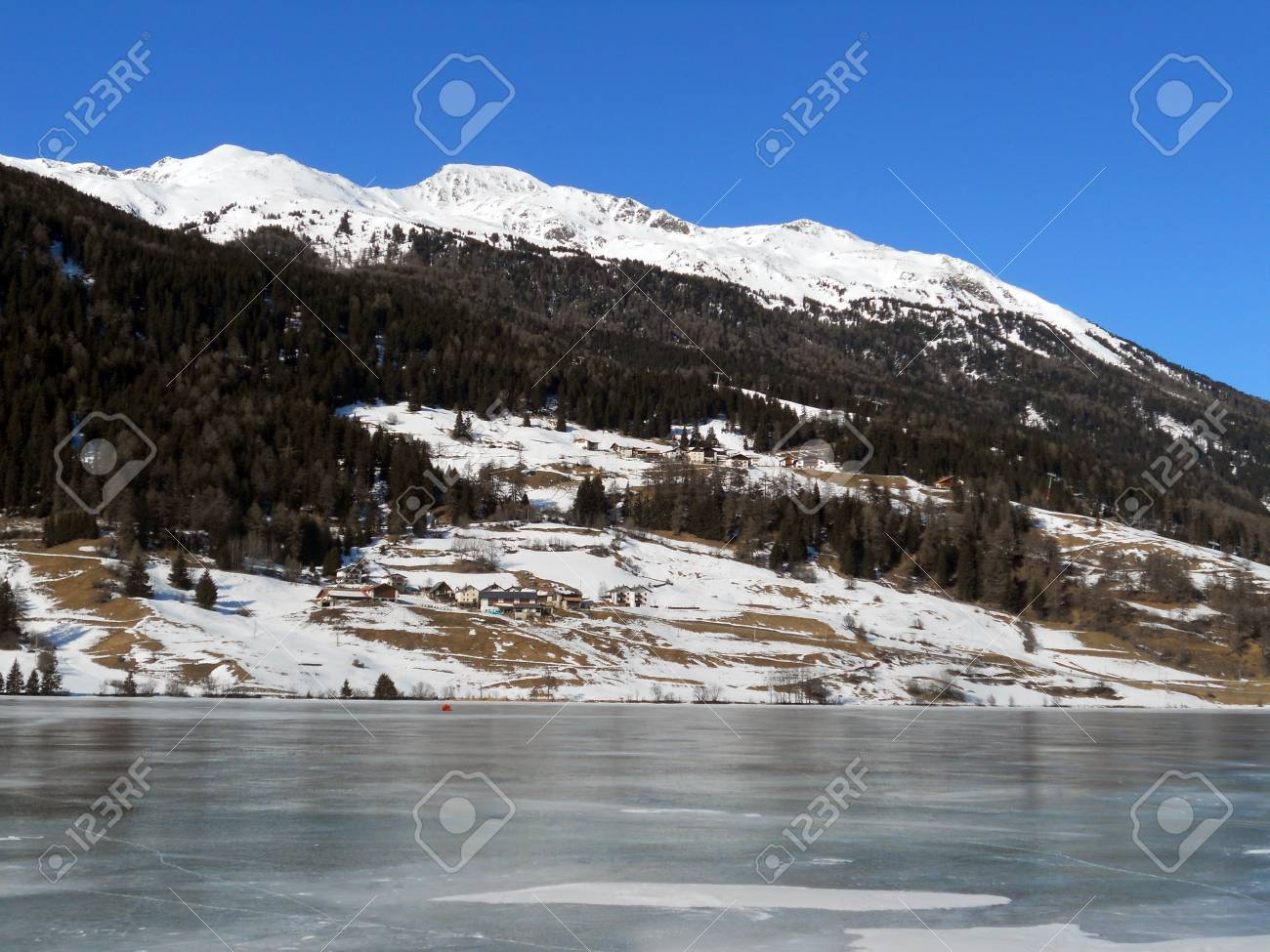 frozen lake in winter with blue sky and snow-capped mountains, Reschensee Stock Photo - 8954998