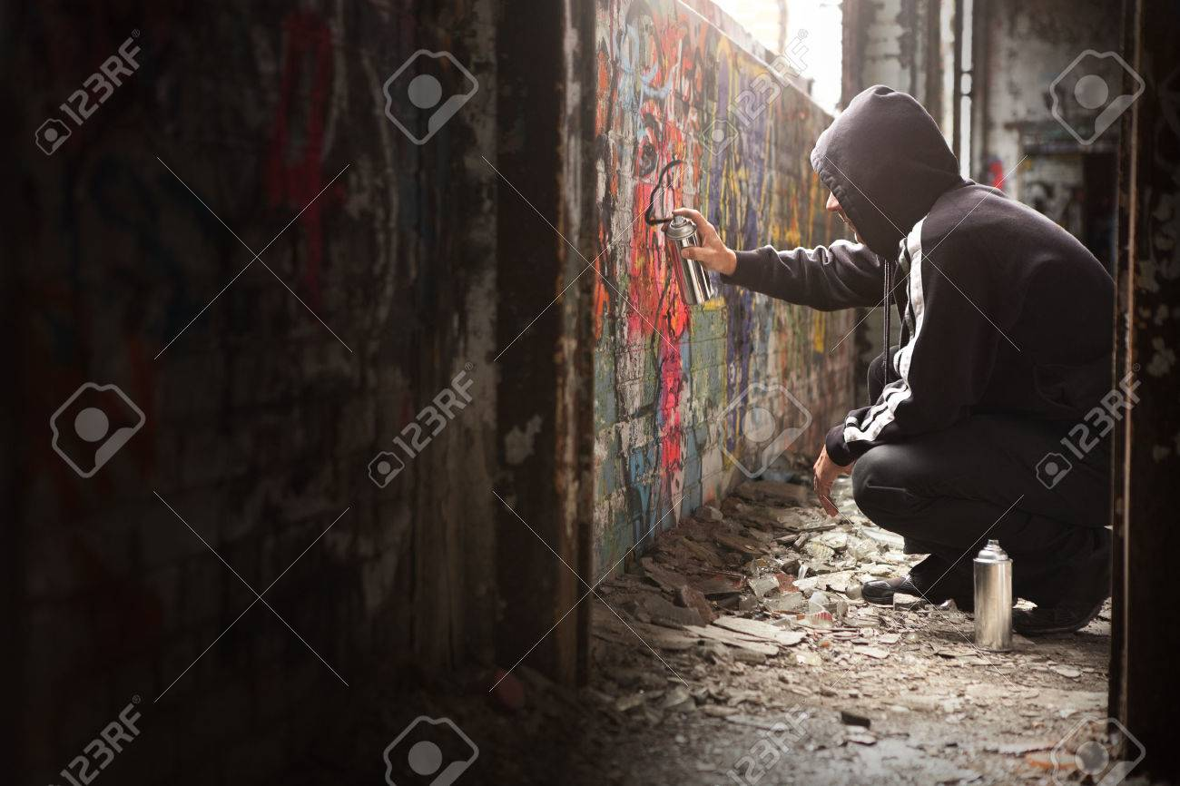 Graffiti wall text - Illegal Young Man Spraying Black Paint On A Graffiti Wall Room For Text