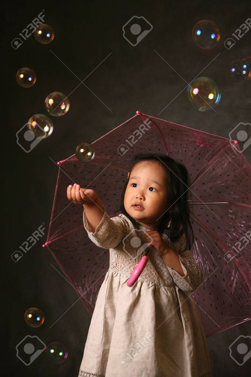 The small Korean girl with a umbrella and soap bubbles Stock Photo - 1000656