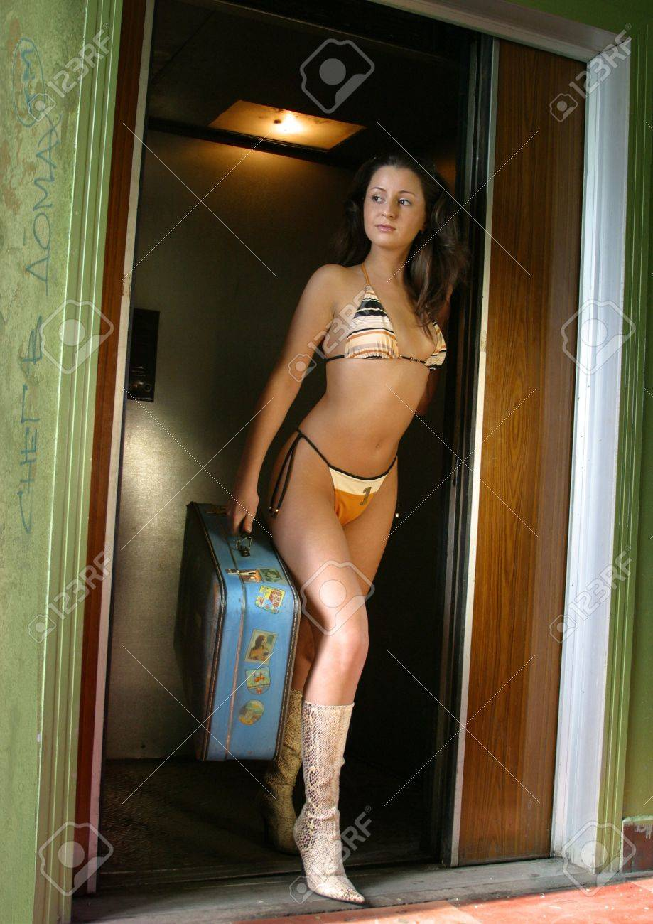 The girl in a bathing suit with a suitcase leaves the lift Stock Photo - 1291045