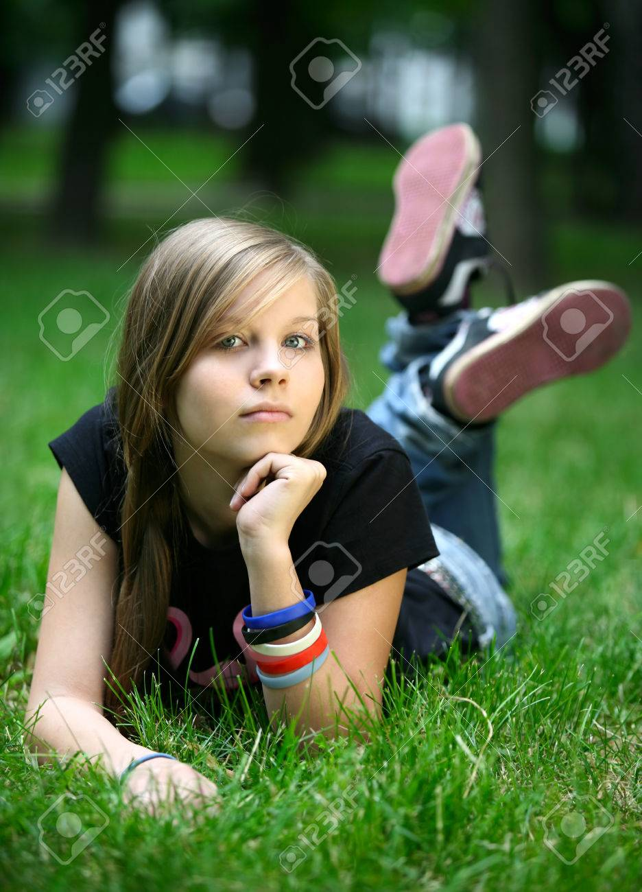 The girl - teenager lays in a grass. Stock Photo - 1590787
