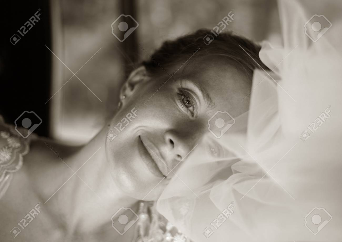 The beautiful bride in a veil gently smiles Stock Photo - 1599809