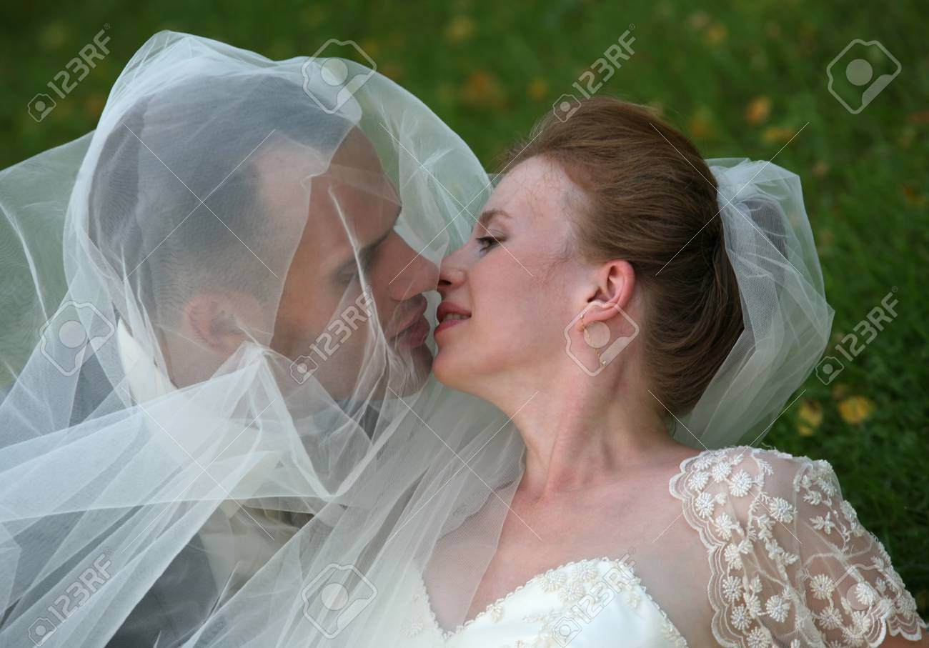 The groom and the bride kiss having closed by a veil Stock Photo - 1599819