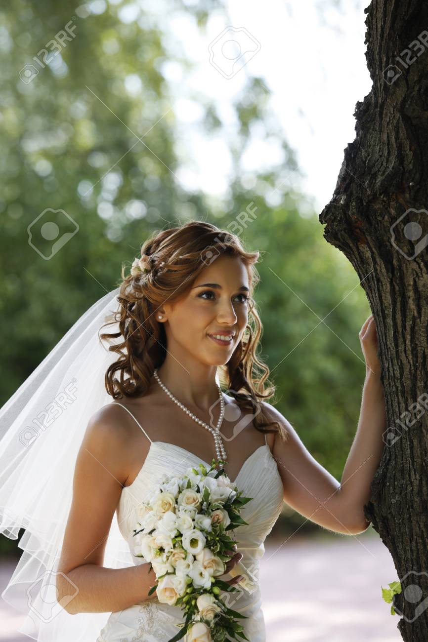 The beautiful bride with bouquet in park Stock Photo - 7696299