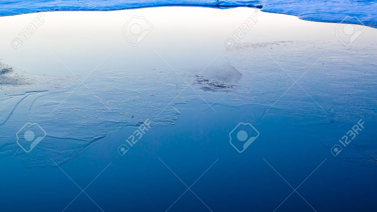 Thin ice in the water reflecting the clear blue sky Stock Photo - 18151093