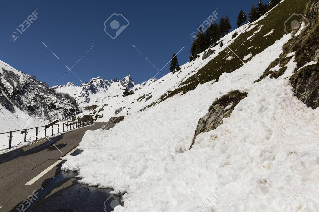 a snow slide blocks a road in the alps of switzerland stock photo