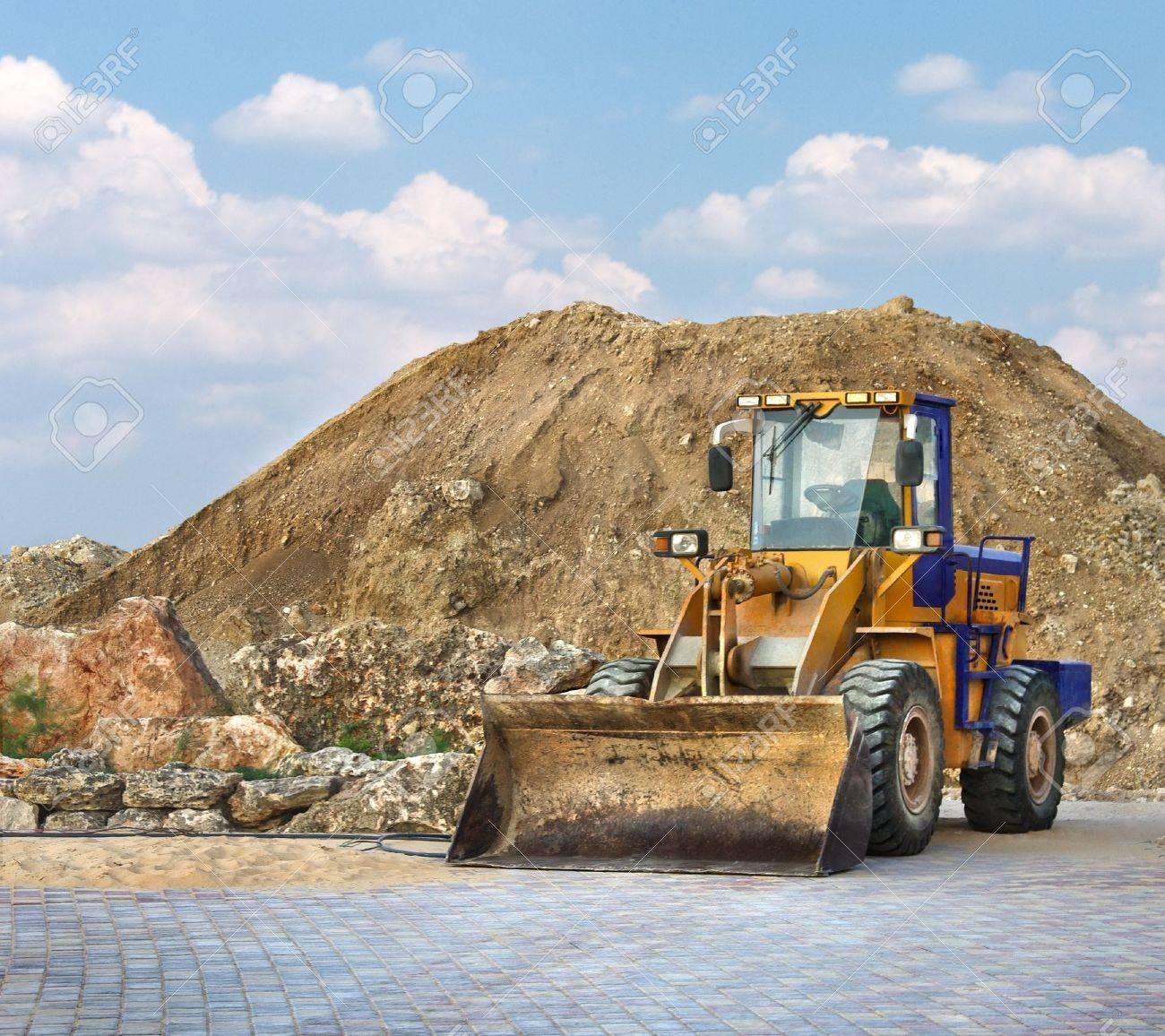 Bulldozer amarillo en una obra de construcción trabajando en un montón de grava. Construcción de escena con una excavadora pequeña. Foto de archivo - 13362426