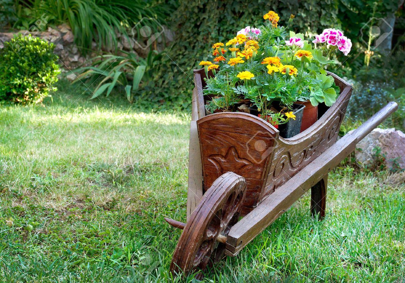 carretilla de madera con flores para el diseo de jardines foto de archivo
