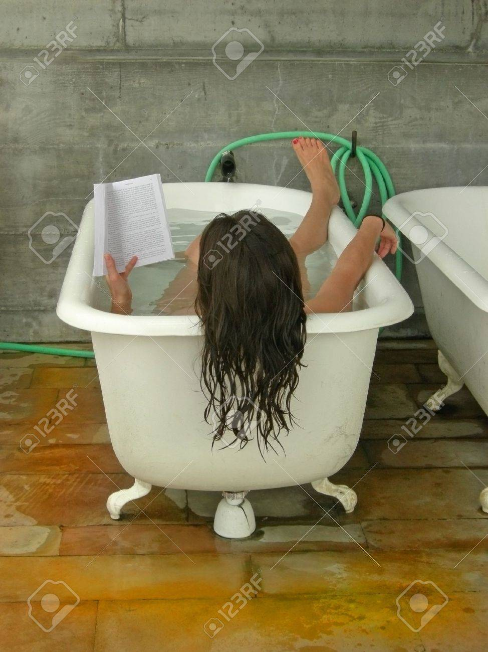 A woman soaks in a tub while reading. Stock Photo - 704702