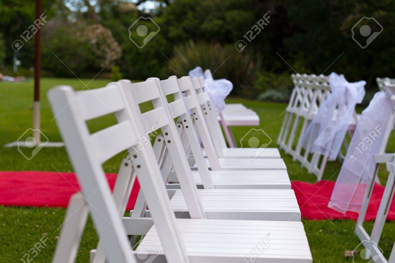 Wedding garden chairs - Chairs With White Ribbons In An Outdoor Garden Wedding Stock Photo 11128916