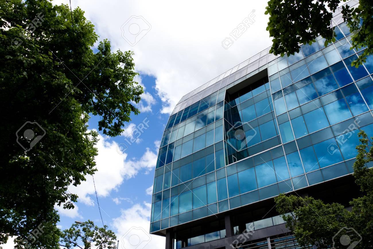 Immeuble de bureaux entourés de beaucoup darbres sous le ciel bleu