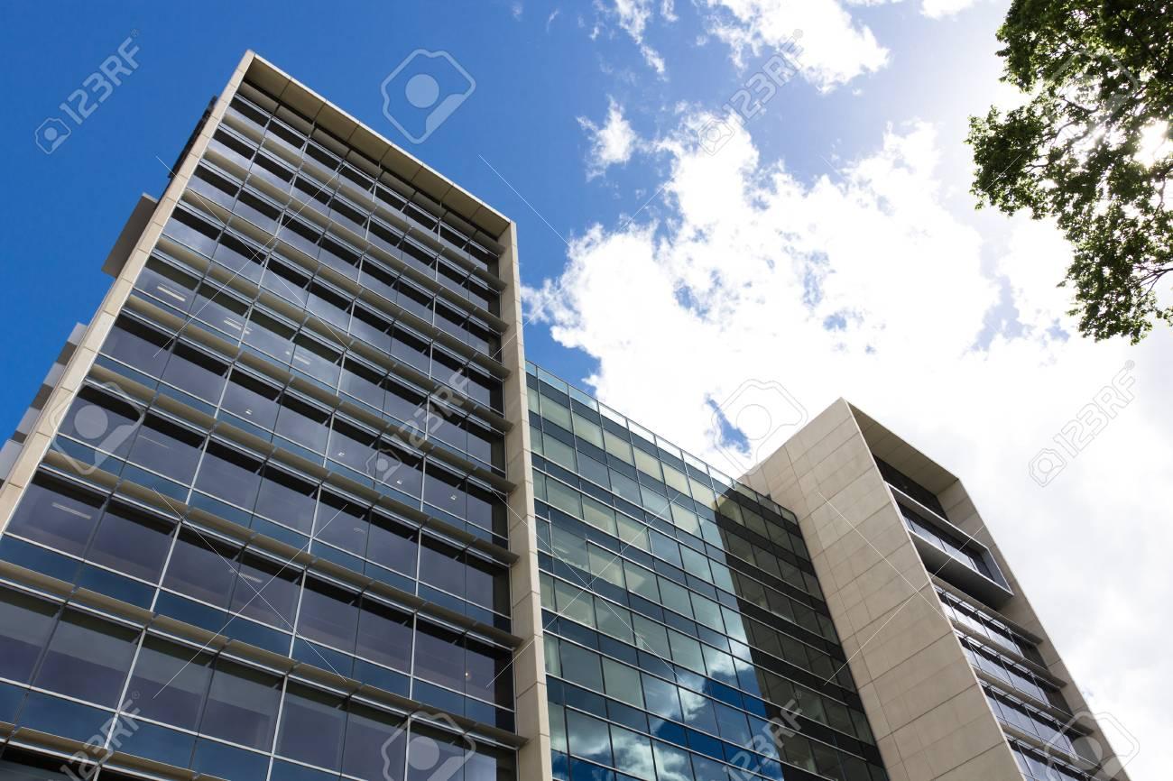 Une tour de bureaux vue de dessous qui reflète le bleu du ciel et de