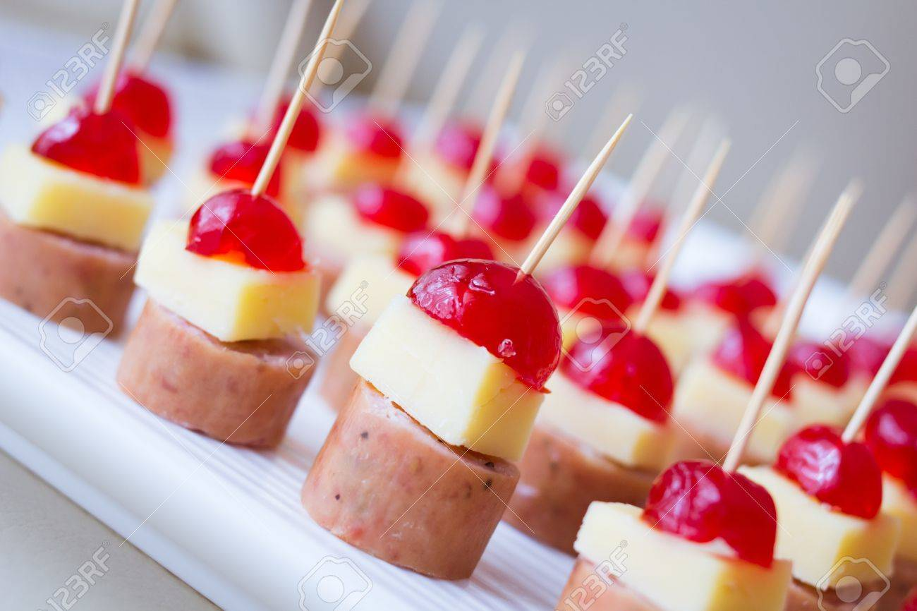 Appetizers with cherry, cheese and salami skewed on a toothpick placed in a tray - 17311912