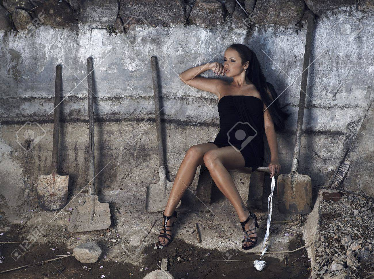 Sexual girl in black dress inside stone quarry among old shovels. Photo. Stock Photo - 7395988