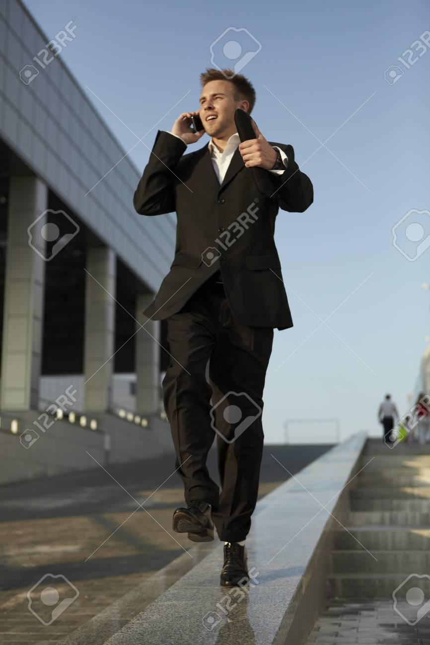 Young businessman calling on mobile phone, outdoor. Stock Photo - 7549522