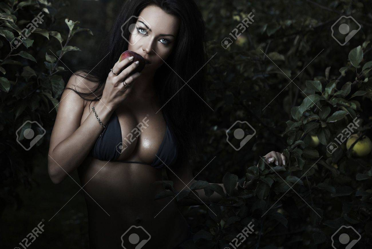 Sexual beauty dressed bikini poses in an autumn garden of apples. Stock Photo - 8091697