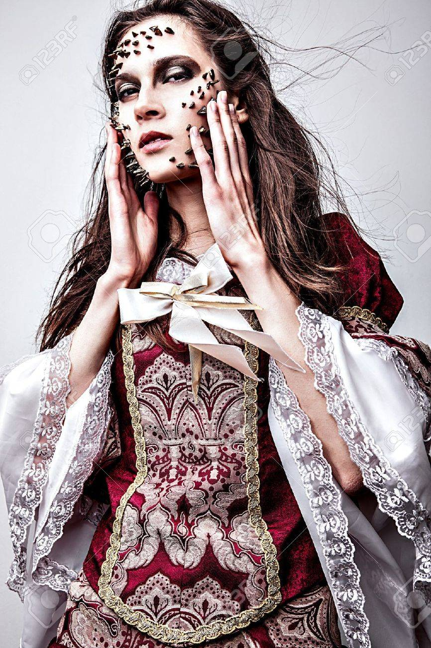 a young lady in medieval dress with thorns of roses on her face Stock Photo - 15598429