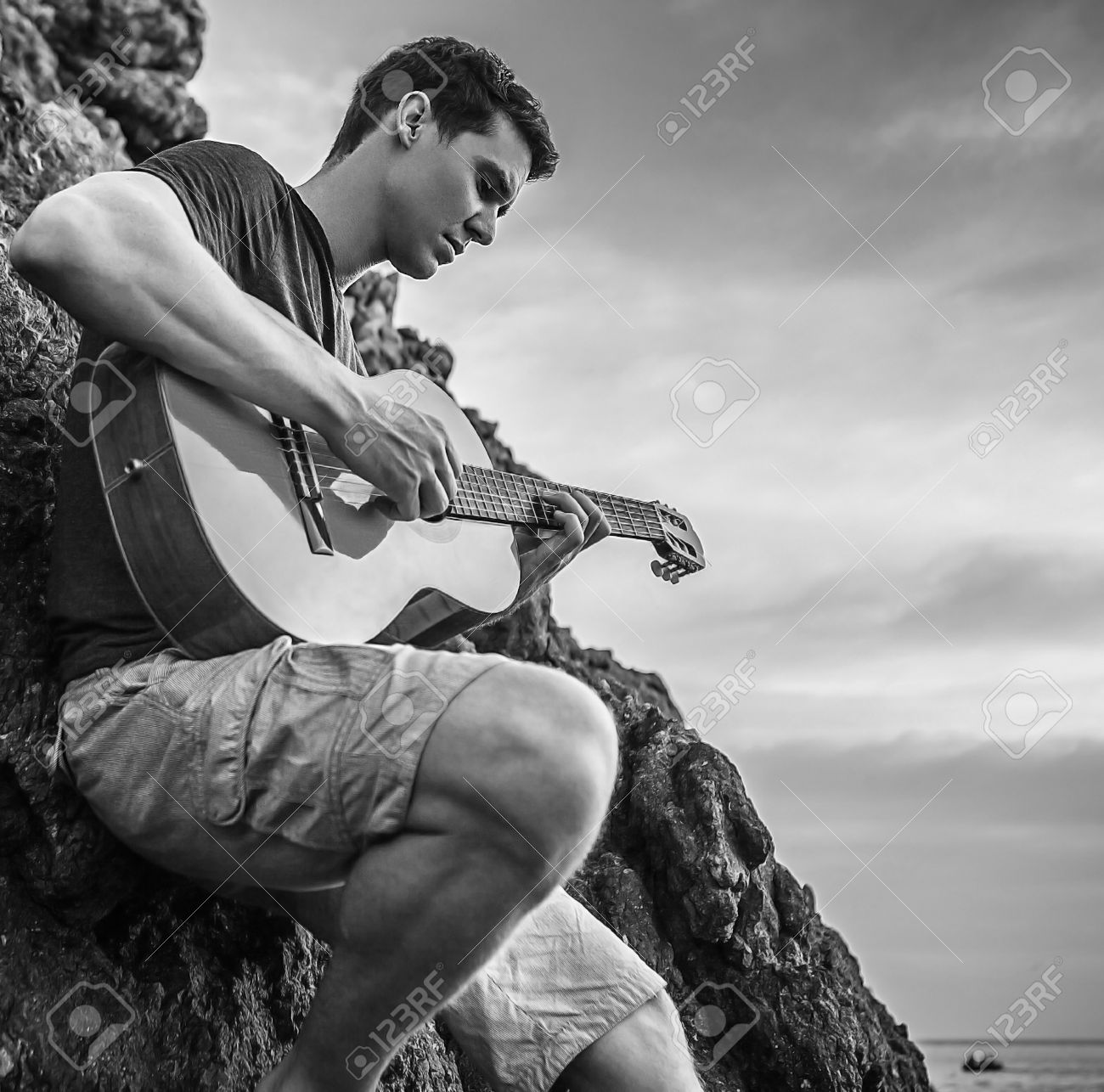 Handsome romantic man pose near evening beach with guitar