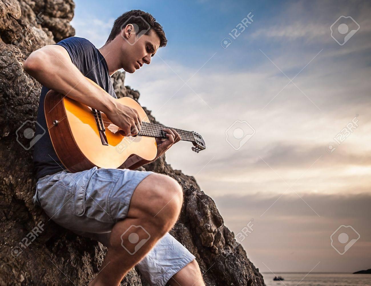Attractive romantique guitariste jeu implantation de la musique sur la plage de roche Banque d'images - 19119955