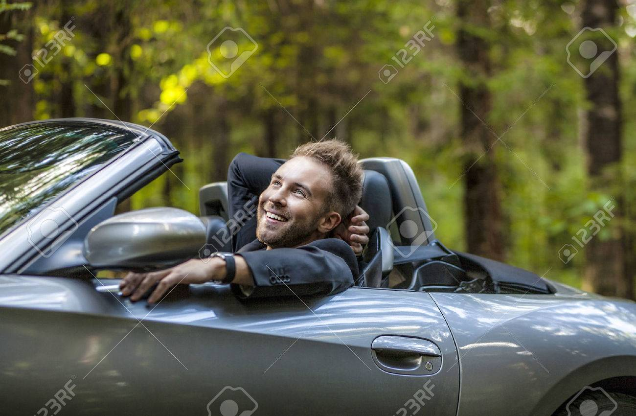 Elegant young happy man in convertible car outdoor Banque d'images - 22572215