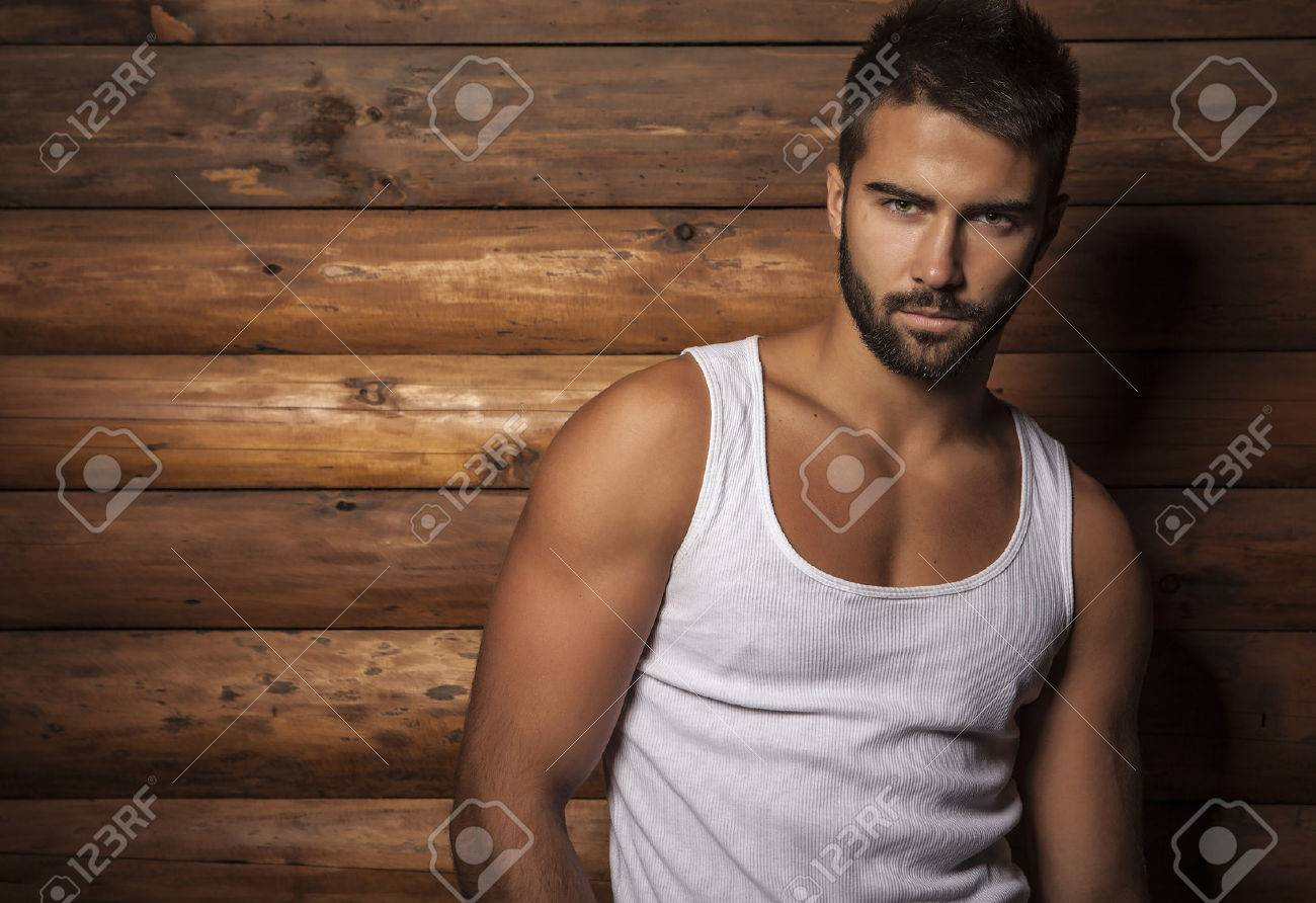 Portrait of young beautiful fashionable man against wooden wall Banque d'images - 22572466