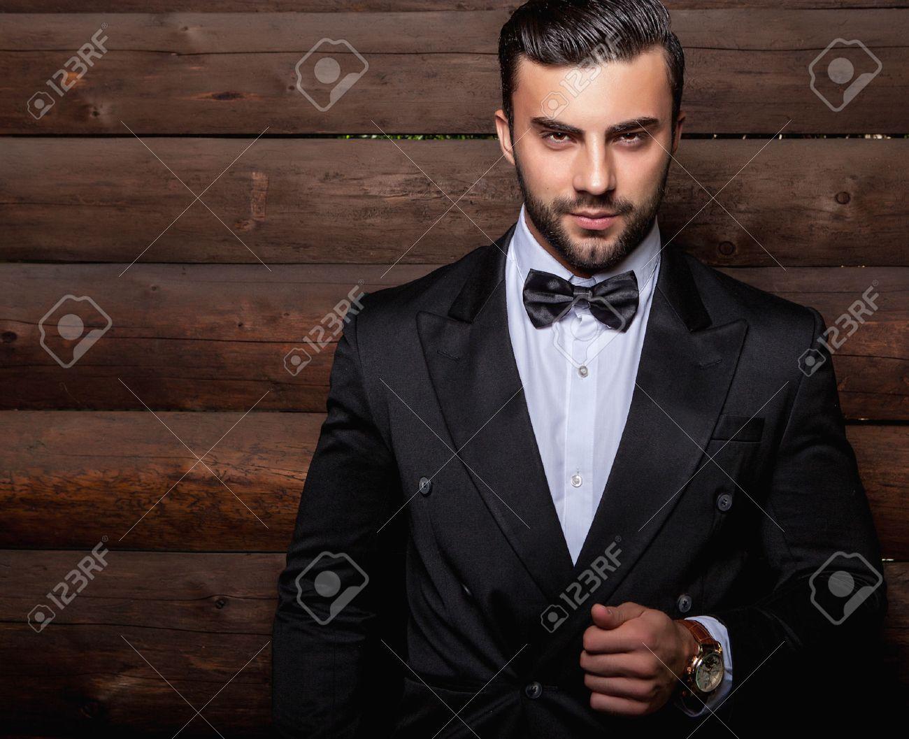 Portrait de la belle jeune homme à la mode contre le mur en bois En costume noir noeud papillon. Banque d'images - 47775991