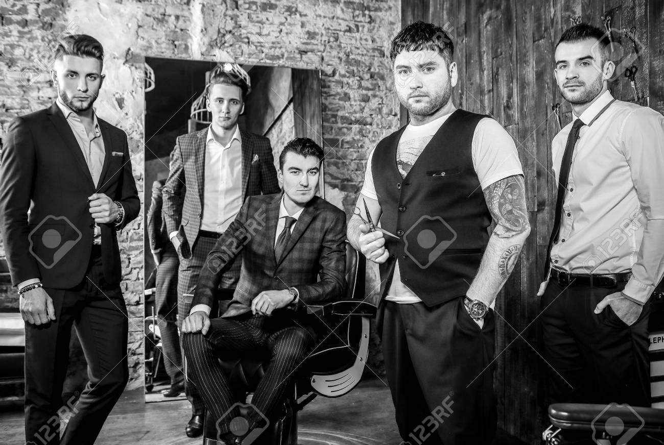 Group of young elegant positive mens pose in interior of barbershop black white photo