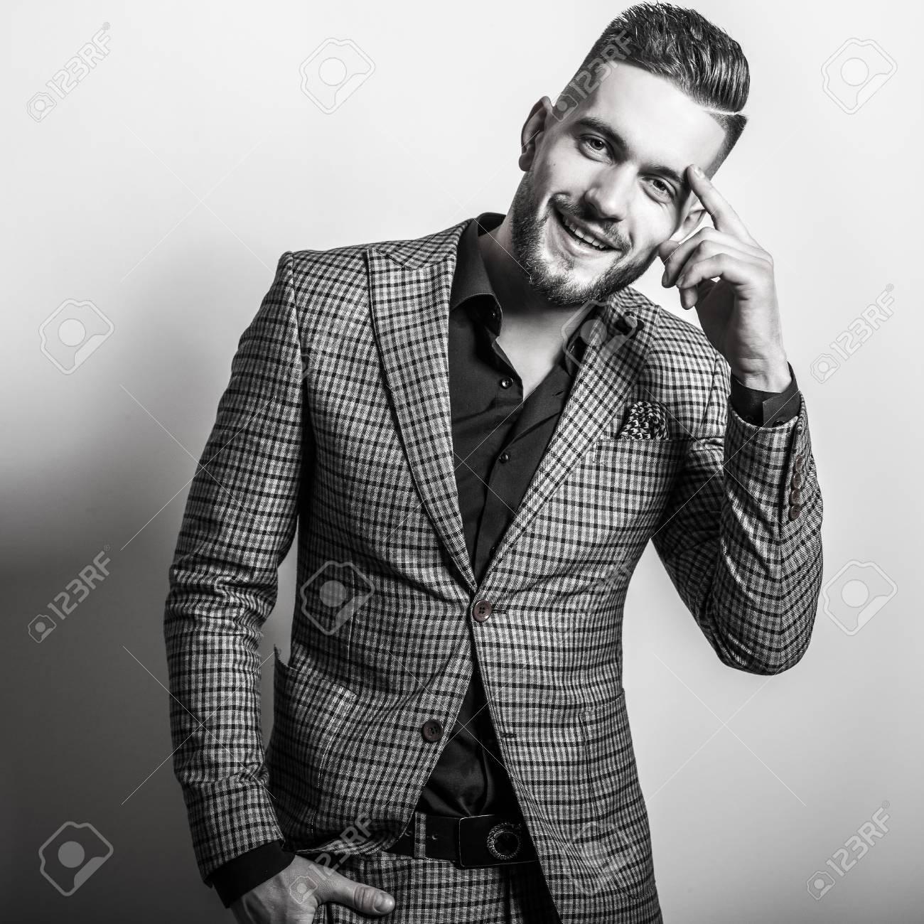 Handsome young elegant man in grey jacket pose against studio background black white portrait