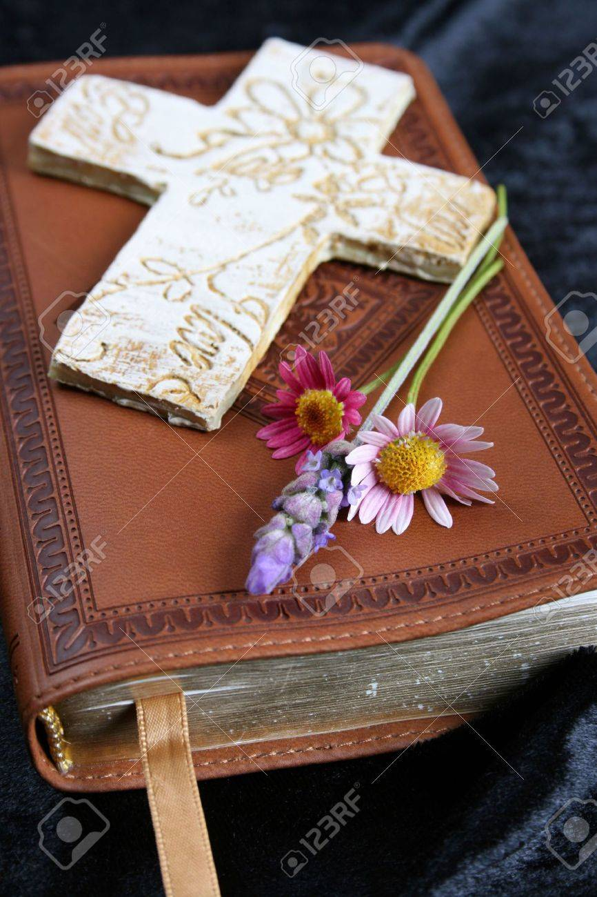 ornate cross on a leather bound bible with flowers stock photo
