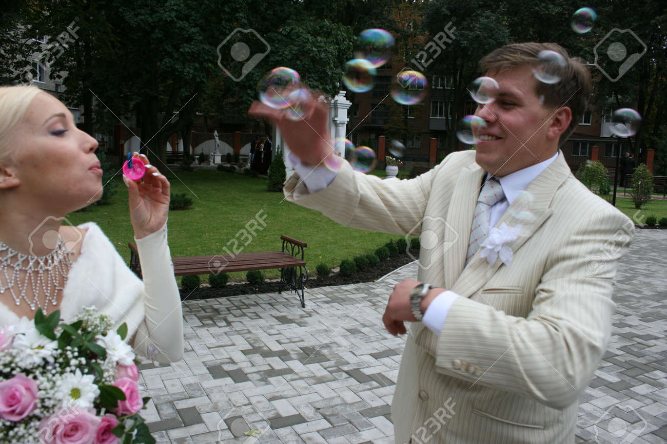 Newlyweds outdoors in wedding day playing with soap bubbles Stock Photo - 2287277