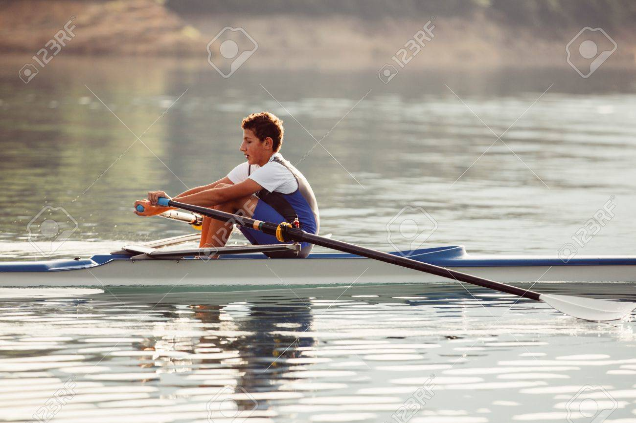 A Young single scull rowing competitor paddles on the tranquil