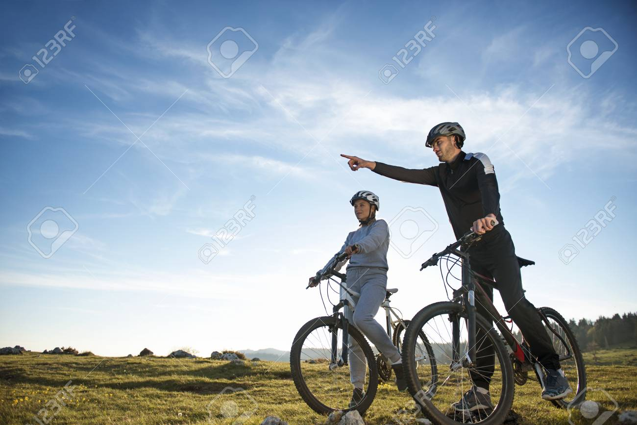 Biker Couple With Mountain Bike Pointing In Distance At Countryside Stock Photo Picture And Royalty Free Image Image 84439666