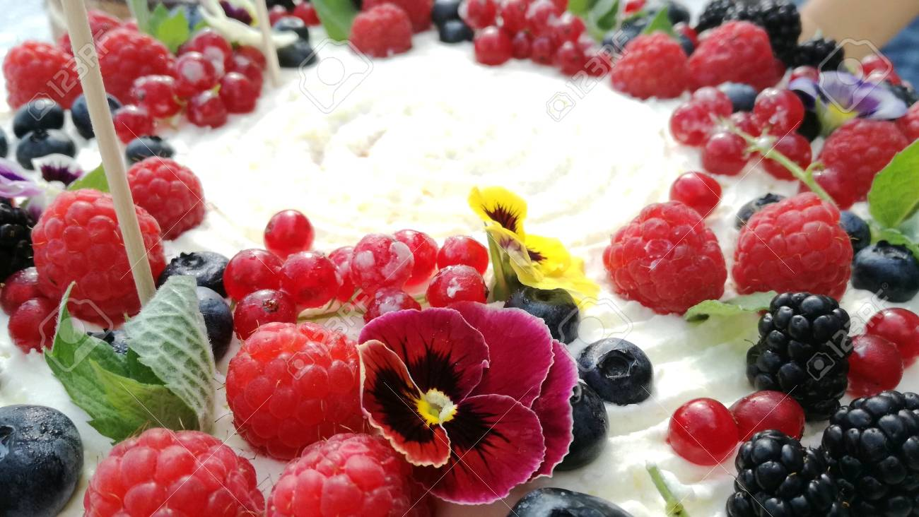 Detailed View On Colorful Fruit Birthday Cake With Cream Coating And Flowers Standard Bild