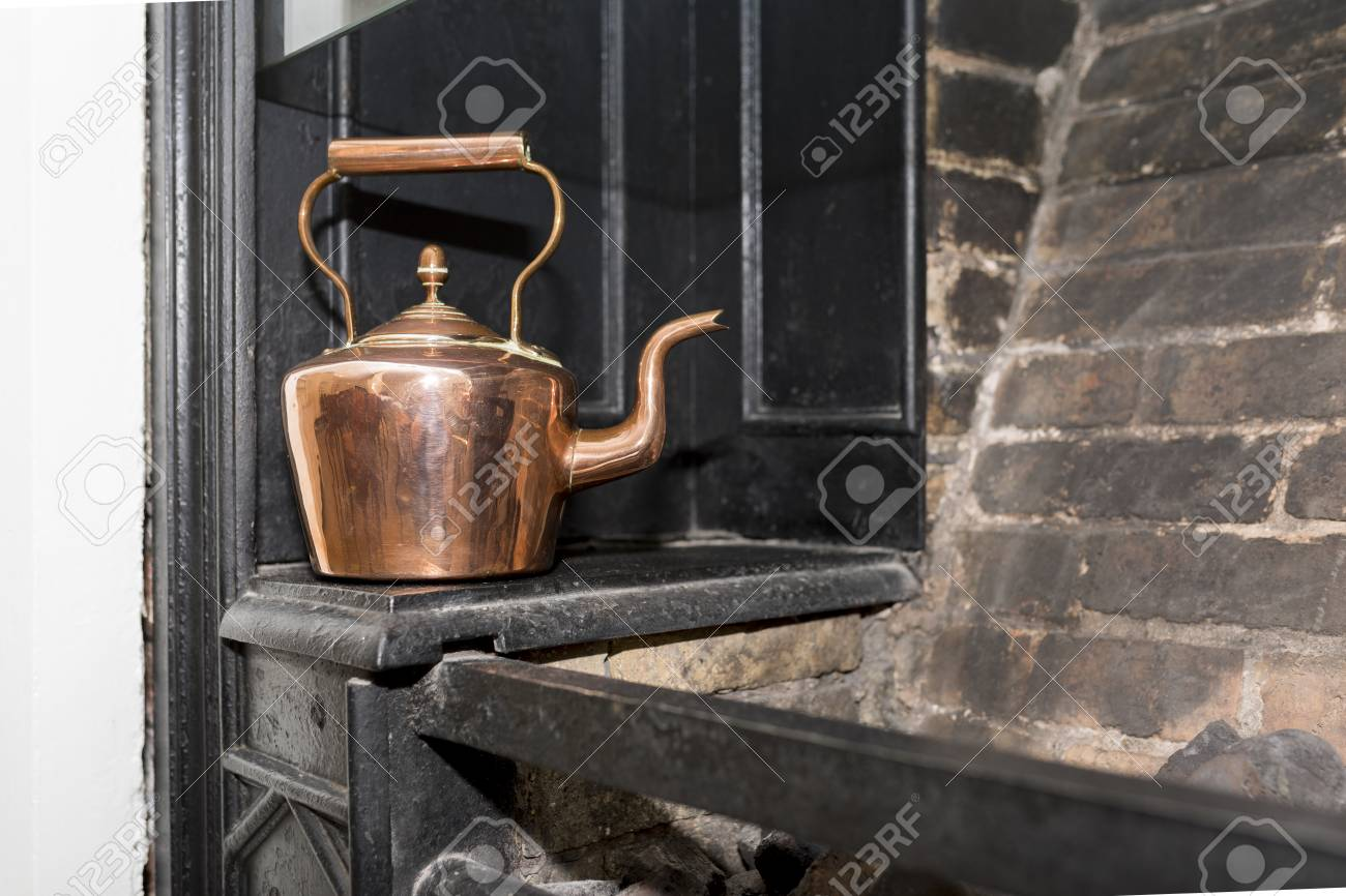 Vintage And Antique Copper Kettle On A Victorian Stove In A Traditional