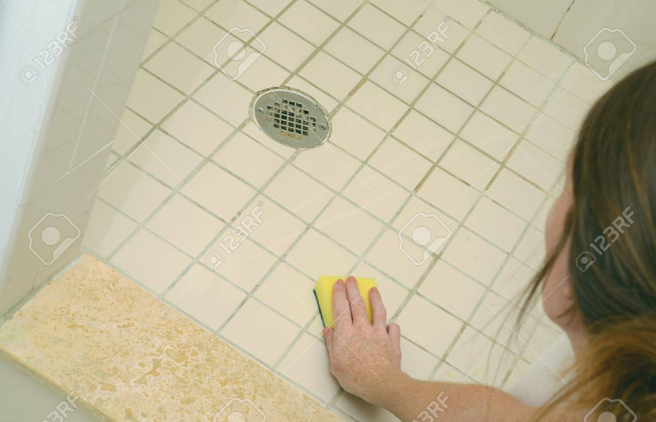 Stock Photo   Woman Scrubbing Soap Scum From A Dirty Shower Floor With  Scour Pad